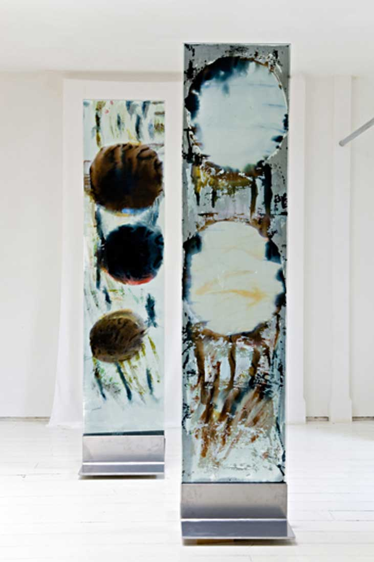 A pair of freestanding glass panels on steel plinths with encapsulated hand painted silks