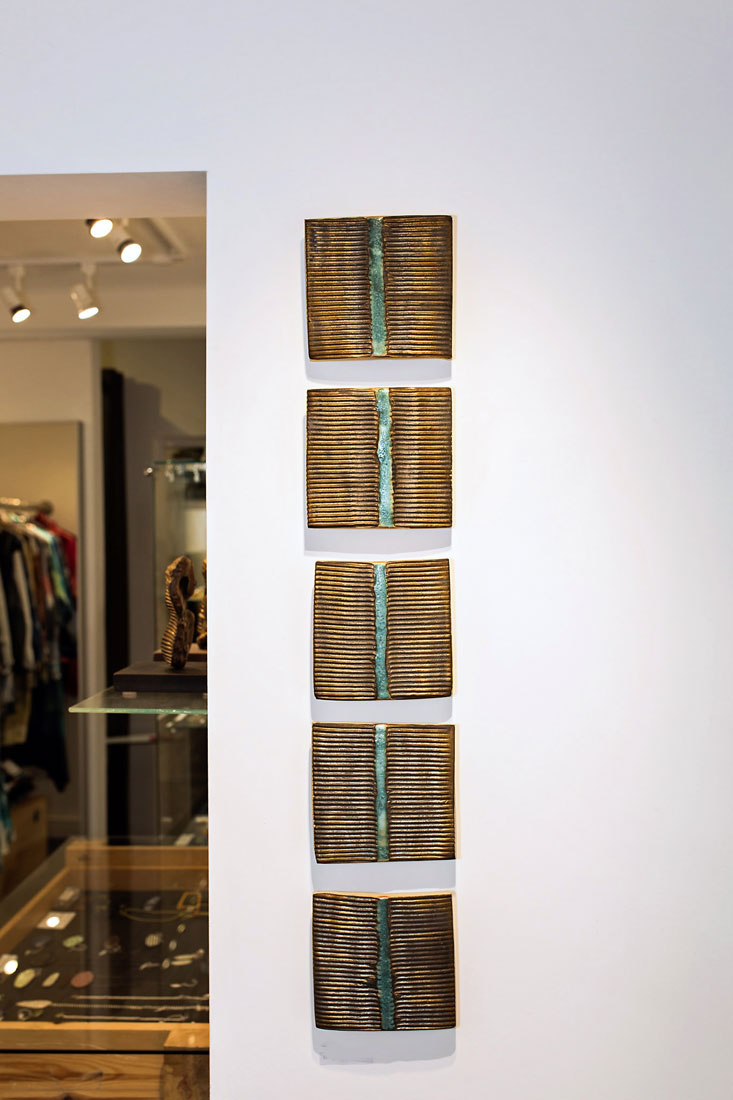 'Bridge' by Gary Wood. Five hand painted ceramic wall tiles in bronze and blue, designed to be displayed vertically.