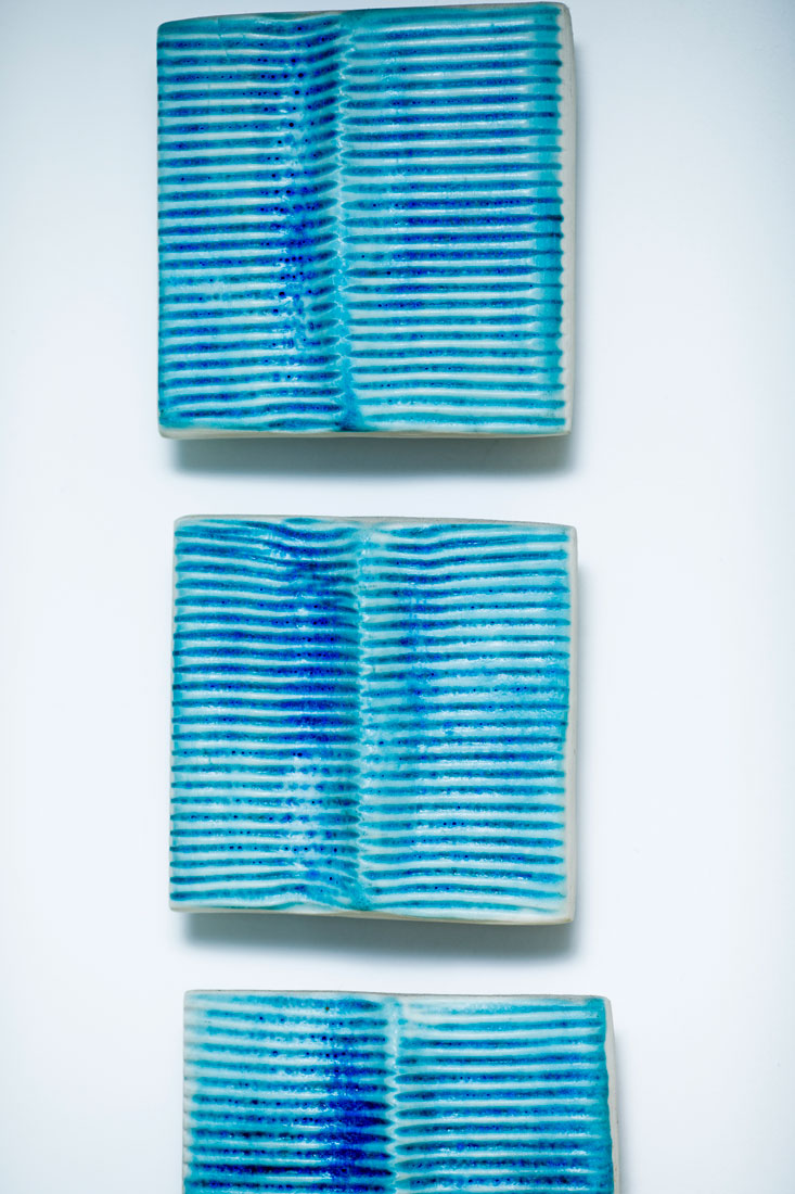 Closeup of three vertical blue ceramic wall panels installed at stillpoint bath by Gary Wood